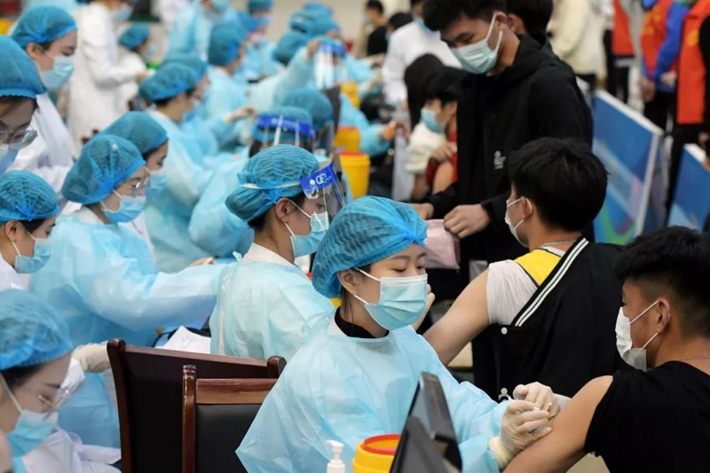 Profissionais de saúde aplicam vacinas em estudantes em Qingdao, na China — Foto: Reuters